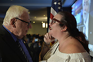 Garden City, New York, USA. November 6, 2018. Nassau County Democrats watch Election Day results at Garden City Hotel, Long Island. NYS Senator JOHN BROOKS, who won re-election to NYS Senate SD8, is talking with LAURA CORCORAN-DOOLIN.