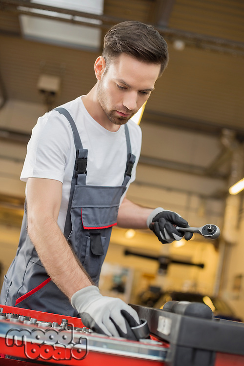 Young male maintenance engineer arranging tools in drawer at car workshop