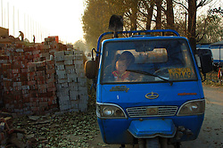 China, Beijing, Ping Fang Xiang, 2008. A brick delivery three-wheeler takes a break near new construction on the north side of Chao Yang Bei Lu..