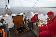 "Crew members playing chess during a quiet moment aboard the ""Lili Marleen"" (luxurious sailing ship of Deilmann Cruises)."