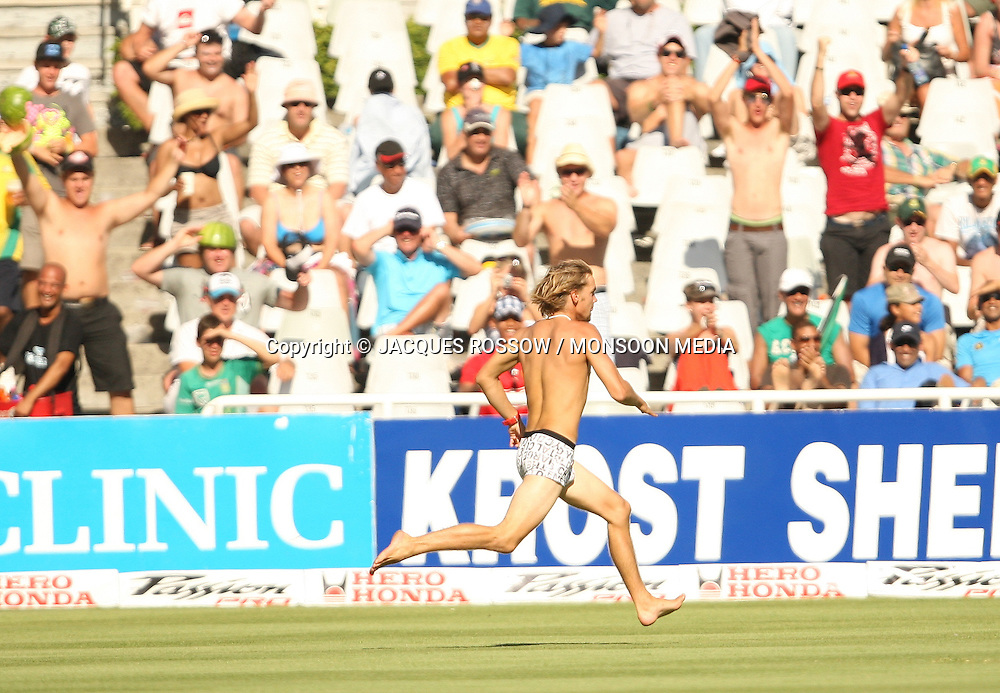 A spectator running across the field during Day 2 of the third and final Test between South Africa and India played at Sahara Park Newlands in Cape Town, South Africa, on 2 January 2011. Photo by Jacques Rossouw / MONSOON MEDIA