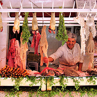 Butcher in Raw Meat Stand at Old Medina in Casablanca, Morocco<br /> This butcher at Casablanca&rsquo;s Old Medina was extremely proud of his display of skinned cow and lamb legs, hanging octopi and other raw, unidentifiable animal parts.  He gave me his business card and requested a copy of this photo. I have no idea if he ever received it. The Old Medina is near Place des Nations Unies.