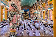 "29 MARCH 2012 - TAY NINH, VIETNAM:  Cao Dai clergy, in colored robes, and adherents, in white, during noon services at the Cao Dai Holy See in Tay Ninh, Vietnam. Cao Dai (also Caodaiism) is a syncretistic, monotheistic religion, officially established in the city of Tây Ninh, southern Vietnam in 1926. Cao means ""high"" and ""Dai"" means ""dais"" (as in a platform or altar raised above the surrounding level to give prominence to the person on it). Estimates of Cao Dai adherents in Vietnam vary, but most sources give two to three million, but there may be up to six million. An additional 30,000 Vietnamese exiles, in the United States, Europe, and Australia are Cao Dai followers. During the Vietnam's wars from 1945-1975, members of Cao Dai were active in political and military struggles, both against French colonial forces and Prime Minister Ngo Dinh Diem of South Vietnam. Their opposition to the communist forces until 1975 was a factor in their repression after the fall of Saigon in 1975, when the incoming communist government proscribed the practice of Cao Dai. In 1997, the Cao Dai was granted legal recognition. Cao Dai's pantheon of saints includes such diverse figures as the Buddha, Confucius, Jesus Christ, Muhammad, Pericles, Julius Caesar, Joan of Arc, Victor Hugo, and the Chinese revolutionary leader Sun Yat-sen. These are honored at Cao Dai temples, along with ancestors.     PHOTO BY JACK KURTZ"