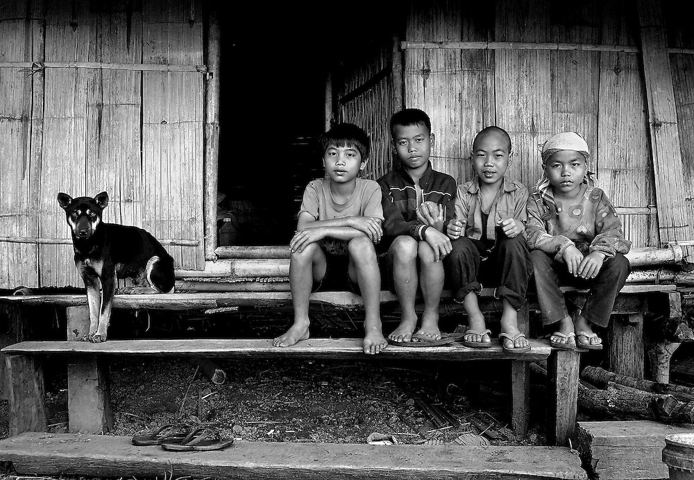 Poor rural village friends and their dog sit outside a boys bamboo home in a village near Hongsa, Laos.