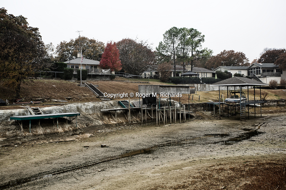 The owners of lakefront homes in the town of Azle, Texas, saw their water disappear as creeks that fed the lake dried up. The creek supplied millions of gallons of water used by energy companies fracking for oil and gas. In addition, a series of intense earthquakes that have rocked the region have been blamed on underground wastewater wells and the drilling. A boom in oil and gas drilling across the American West has led to pollution and environmental problems in what were once pristine lands. Traveling rigs go from location to location, drilling down into the shale rock, and are soon followed by pumps that inject a toxic brew of water and chemicals for hydraulic extraction or 'fracking' of oil and gas. Photograph by Roger M. Richards