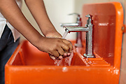 A schoolboy washing his hands with clean water in a Splash sink