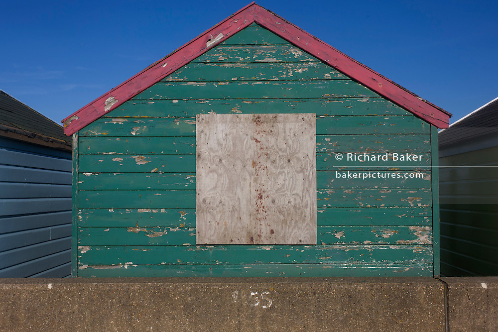 Neglected but expensive real estate beach hut at the Suffolk seaside town of Southwold, Suffolk.