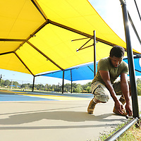 Vonjacques Hall, an employee with Ivy Fence in Tupelo, tightens bolts on the fencing post as he works with fellow employee's Carl Scherff and Chris Hughes installing the new fence around the Basketball courts at Gumtree Park in Tupelo Monday morning.