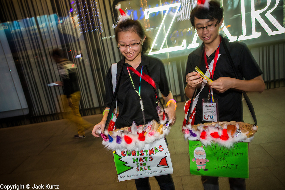 """22 DECEMBER 2012 - SINGAPORE, SINGAPORE:   Volunteers sell Christmas hats for charity during """"Christmas on a Great Street"""" on Orchard Road in Singapore. Businesses on Orchard Road, Singapore's famed shopping street, sponsors the annual event. The street is decorated with holiday lights, stores stay open late and crowds pack the area. This is the 8th year Singapore has held the """"Christmas on a Great Street"""" event.  PHOTO BY JACK KURTZ"""