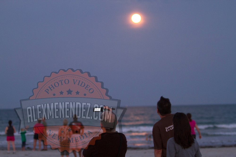 Spectators film on the beach under a rising moon as the United Launch Alliance Delta 4 rocket lifted off this evening from launch complex 37 to deliver a military communications satellite into orbit to cover the Americas. The launch occurred at 8:27 p.m. from Cape Canaveral, Florida on Friday, May 24, 2013. This is a general view from Jetty Park in Cape Canaveral.  (AP Photo/Alex Menendez)