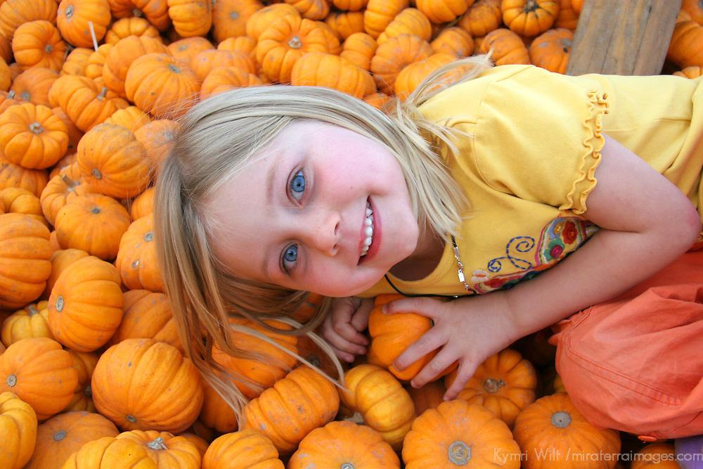 USA, California, Encinitas.  A young girl enjoys a local pumpkin patch carnival.