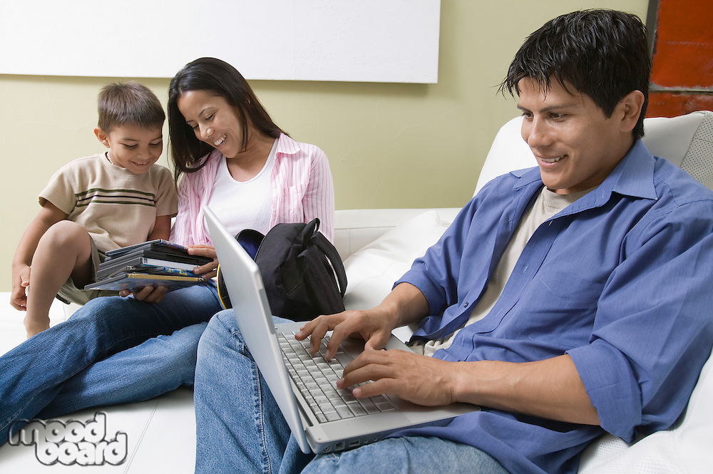 Family Using Laptop and Looking at DVD's on Couch