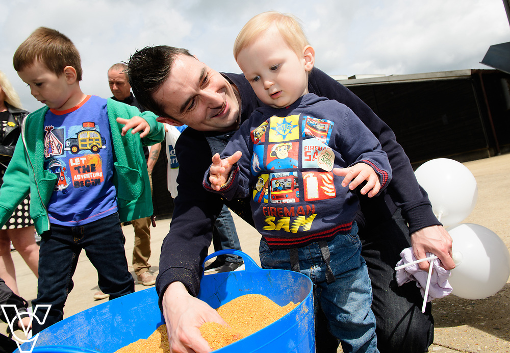 As part of Open Farm Sunday, May Park's Barr Farm in Billinghay, Lincolnshire, was open to the public.  Pictured is Neil Hamson with his son Jamie (one) looking at the feed.<br /> <br /> PIcture: Chris Vaughan Photography<br /> Date: May 21, 2017