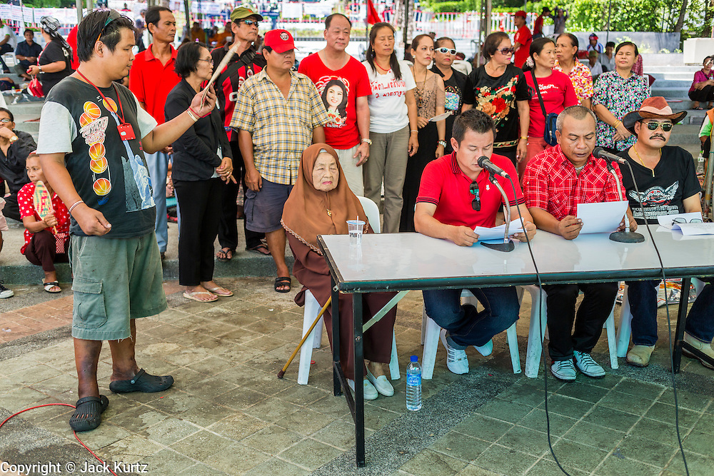 01 MAY 2013 - BANGKOK, THAILAND:  Red Shirts leades are fanned by a supporter during a press conference in front of the Constitutional Court. Several hundred Thai Red Shirts, members of the United Front for Democracy against Dictatorship (UDD), have been camped out at Thailand's Constitutional Court, which oversees matters related to the Thai constitution and constitutional amendment. The Red Shirts are protesting the court's decision to consider a petition regarding the constitutionality of the constitutional amendments that have been proposed by the government. The group is arguing that by considering the petition, the Court is impeding the powers of the legislative branch.  PHOTO BY JACK KURTZ