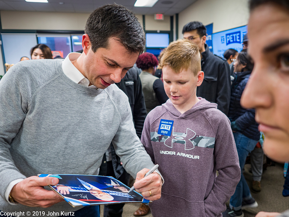 28 DECEMBER 2019 - DES MOINES, IOWA: Mayor PETE BUTTIGIEG, left, signs a photo for a teenager during a meet and greet with Buttigieg in Des Moines. Buttigieg talked to a crowd of about 75 people at Urban Dreams, an African-American community empowerment center in Des Moines. It was a part of Buttigieg's continuing outreach to African-American voters. Buttigieg, the mayor of South Bend, Indiana, is running to be the Democratic nominee for President in the 2020 election. Iowa traditionally holds the first presidential selection event of the 2020 election cycle. The Iowa Caucuses are on Feb. 3, 2020.           PHOTO BY JACK KURTZ