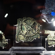 One of the highlights of the National Archaeological Museum in Athens, Greece, the Antikythera Mechanism now has its own dedicated exhibit gallery in which all of its fragments are on display. Believed to date to somewhere around 100 BC to 205 BC, it was found amongst a large cache of statues, coins, and other artefacts on a sunken shipwreck discovered in 1900 by sponge divers off the coast of the Greek island of Antikythera. It was badly damaged after such a long time in the salt water, but extensive research in recent decades has resulted in a consensus that it is a kind of astronomical analog computer as well as some modern reconstructions. In the center is the piece known as Fragment A, the largest surviving piece and the one that contains most fo the gears.