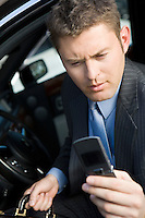 Business man using mobile phone in car