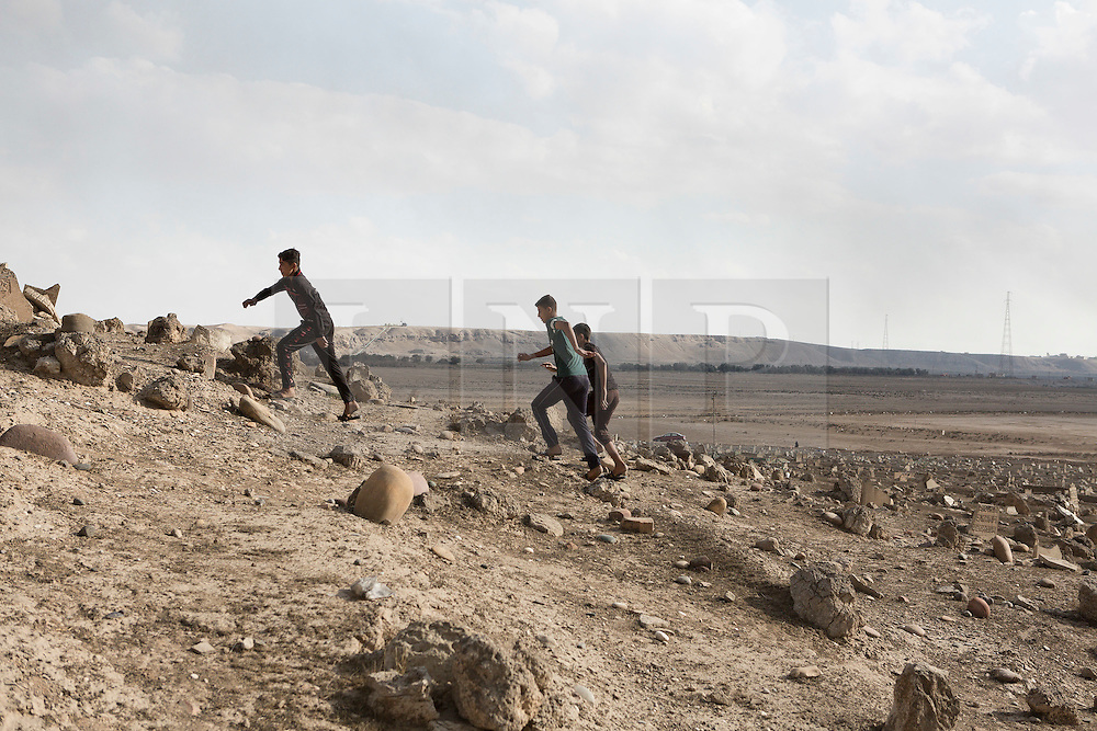 Licensed to London News Pictures. 02/11/2016. Qayyarah, Iraq. Children run amongst vandalised gravestones, smashed by Islamic State militants, in the Qayyarah Cemetery in the town of Qayyarah, Iraq. The headstones were vandalised by the extremists, who believe that a grave should be flat to the earth and without markings, during the towns two year ISIS occupation.<br /> <br /> Two months after being liberated from the Islamic State, the Iraqi town of Qayyarah, located around 30km south of Mosul, is still dealing with the environmental repercussions of their ISIS occupation. The town's estimated 15,000 inhabitants constantly live under, and in, heavy clouds of smoke which often envelope the settlement. The clouds emanate from burning oil wells in a nearby oil field that were set alight by retreating ISIS extremists after a two year occupation. The proximity of the fires, often right next to homes within the town, covers many buildings and residents with thick soot and will lead to long term health and environmental implications. Photo credit: Matt Cetti-Roberts/LNP
