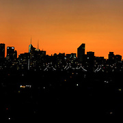 The sun sets behind the Manhattan skyline in New York City as a metro train passes in the foreground near Flushing, New York viewed from Arthur Ashe Stadium  during the US Open Tennis Tournament, Flushing, New York. USA. 10th September 2012. Photo Tim Clayton