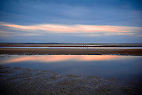 Sunset after a rainstorm and during low tide on First Encounter Beach on Cape Cod