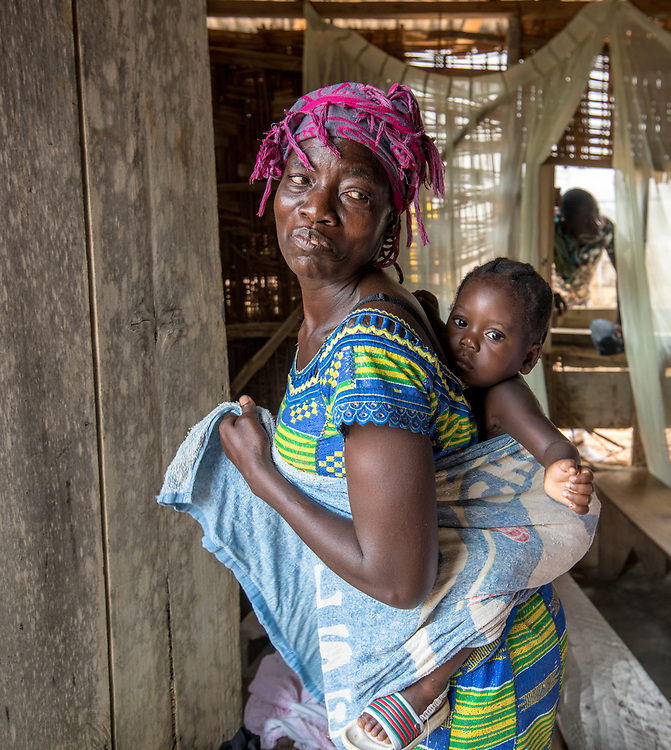 An older woman poses with a baby wrapped to her back in Ganta, Liberia
