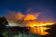 The Pilot Fire's glow is reflected in Silverwood Lake in the San Bernardino National Forest, August 7th, 2016. The Pilot Fire threatened homes in a rural area of San Bernardino county, near the site of other fast-moving wildfires that plagued rural areas of Southern California during the summer. <br /> <br /> The Pilot Fire burns in the San Bernardino National Forest August 7th, 2016 in California. <br /> <br /> Long exposure image.