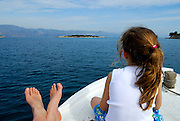 Rear view of Caucasian female (5 years old) sitting on bow of boat next to adult's feet. Adriatic Sea, Croatia.