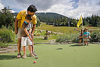Dad and son play a round of mini-golf at the Adventure Zone, Blackcomb Mountain, Whistler, BC Canada.