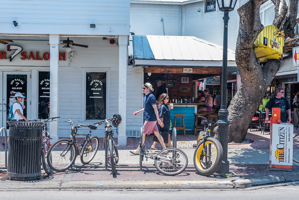 Key West, Florida--April 29, 2018.  Pedestrians are walking along Duval Street. In the background other people are having drinks in a bar. Editorial Use Only.