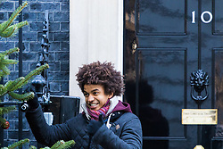 London, December 01 2017. Workers install the Christmas tree outside the door of 10 Downing Street, official residence of the British Prime Minister. The tree comes from the winner of the British Christmas Tree Growers' Association' annual competition for the honour of having a grower's tree at the prestigious address. PICTURED: Blue Peter's Radzi Chinyanganya helps decorate the tree. © Paul Davey