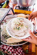 Toppinng of  lotus stems, long beans, cucumbers and wild herbs for fermented rice noodles topped with 'curry' (num banh chok), Siem Reap