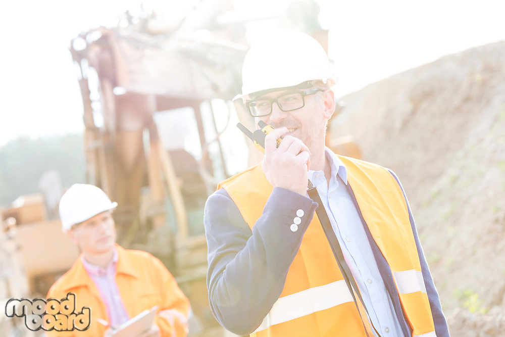 Happy engineer using walkie-talkie on construction site with colleague in background