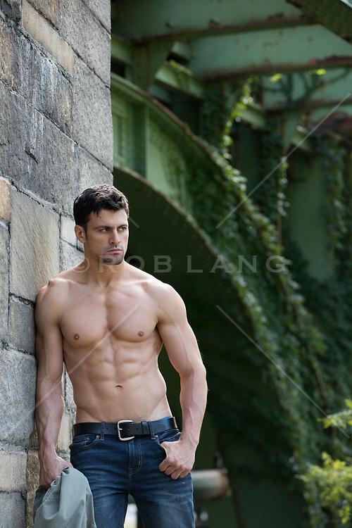shirtless muscular man in an urban setting