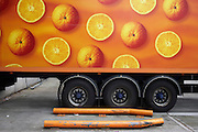 A long-distance lorry is parked at the Sainsbury's 700,000 sq ft (57,500sq m) supermarket warehouse and distribution depot at Waltham Point London England. With round wheels echoing the circles of oranges, long-distance vehicles depart every two minutes, 24 hours a day, 364 days a year to 80 UK stores and handling 2.5m supermarket cases a week. Transporting refrigerated perishable foodstuffs, these lorries are ever-present on the nation's motorways and A-roads, plying back and forth to re-supply the supermarkets. Food orders are conveyed with sorter systems that group products together, ordering them to favour the layout of specific stores, optimising how the shelves are stacked..