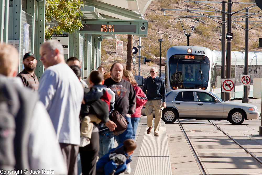 28 DECEMBER 2008 -- PHOENIX, AZ: Metro light rail passengers wait for a train to pull into a station in Tempe, AZ, Sunday. The new Metro Light Rail is 20 miles long and cost $1.4 billion dollars. Construction was funded by local, state and federal monies. The trains will operate on one line through Phoenix and the suburban communities of Tempe and Mesa. The trains started running Saturday, Dec 27, 2008 and will be free until Jan. 1, 2009. The regular fare will be $1.25 for one ride or $2.50 for an all day pass.  Photo by Jack Kurtz / ZUMA Press