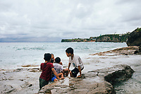 Young boys play in the tide pools at Bingin Beach in Bali, Indonesia.