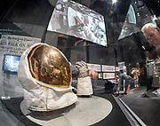 "Dad's charts, maps and photos on display, center, with ""Destination Moon"" at Seattle's Museum of Flight.  ""Buzz"" Aldrin's helmet and gloves, left. Above, film showing Apollo 11 astronauts referring to navigation charts."