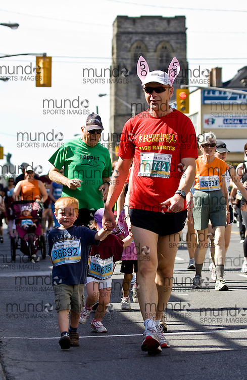 (Ottawa, ON --- May 29, 2010) 10K race pace bunny Bob Plamondon does double duty and paces Michael Plamondon around the kids and community 2km race during the Ottawa Race Weekend. Photograph copyright Sean Burges / Mundo Sport Images