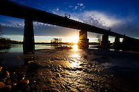 The sun sets under the railway bridge that crosses the Bow River through Refinery Park in SE Calgary.<br /> <br /> &copy;2015, Sean Phillips<br /> http://www.RiverwoodPhotography.com