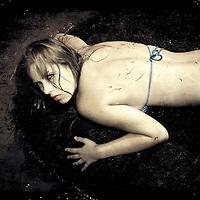 A young girl in a blue bikini lying on rocks at low tide in Hunstanton, a seaside resort on the West Norfolk Coast.