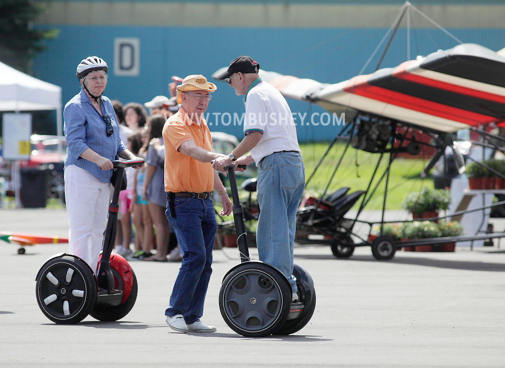 Wurtsboro, NY - An elderly man lets another man try out his Segway Personal Transporter at a festival at Wurtsboro Airport on Aug. 30, 2009.
