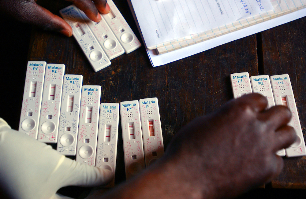 A health post worker separates the positive rapid test kits from the negative ones in a rural health centre in Bie province, Angola.