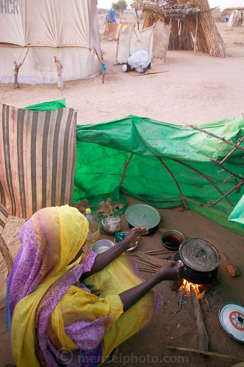 (MODEL RELEASED IMAGE). Squatting before the fire, D'jimia Souleymane stirs a pot of aiysh, the thick porridge that her refugee family eats three times a day. Even when they lived in their village in the Darfur region of Sudan though, aiysh was the mainstay of every meal, along with a thin soup. This is also the traditional meal in central and northern Chad. (From a photographic gallery of kitchen images, in Hungry Planet: What the World Eats, p. 54)