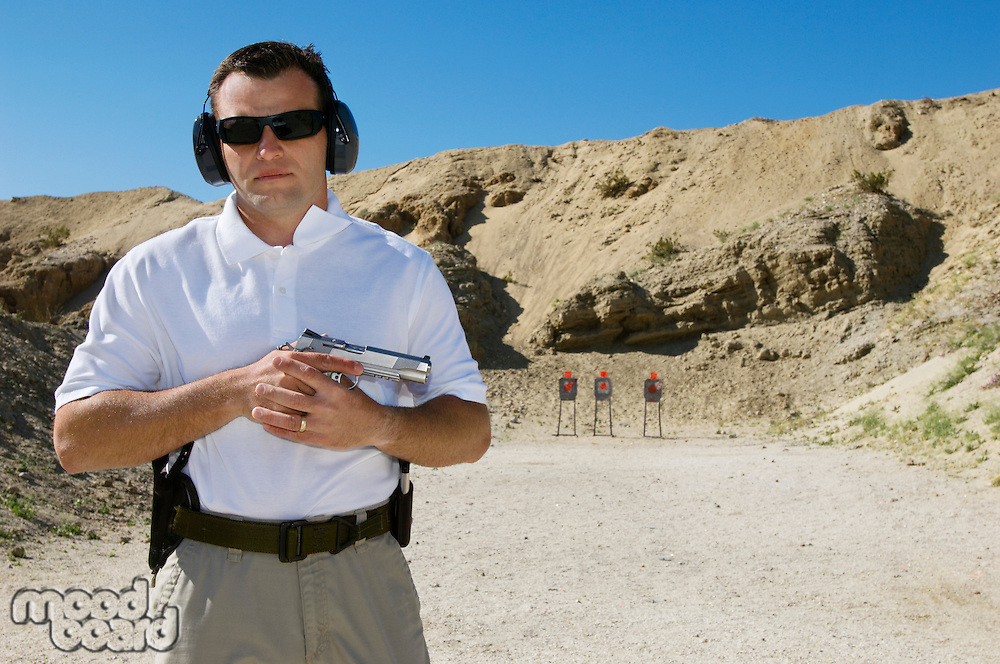 Man holding hand gun at firing range, portrait