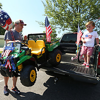 Sam Allen, 4, waits in the truck as his dad Josh unloads his Power Wheel Gator for him to ride in the Joyner Neighborhood Fourth of July Parade on Wednesday morning.