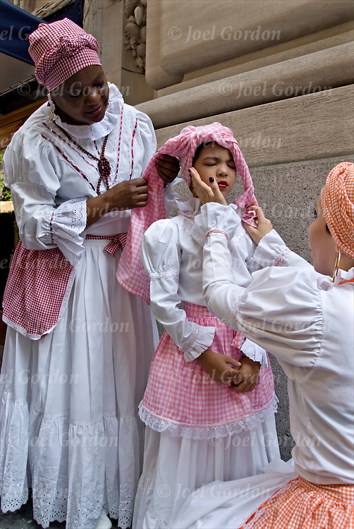 Mother and daughter and friend from the group Hijos de Agueybana in folk costumes before the start of the Puerto Rican Day Parade.