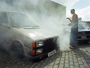 Young man standing in front of a smokey van.