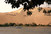 Tourboat and sand dune on the Nile River.Aswan, Egypt.
