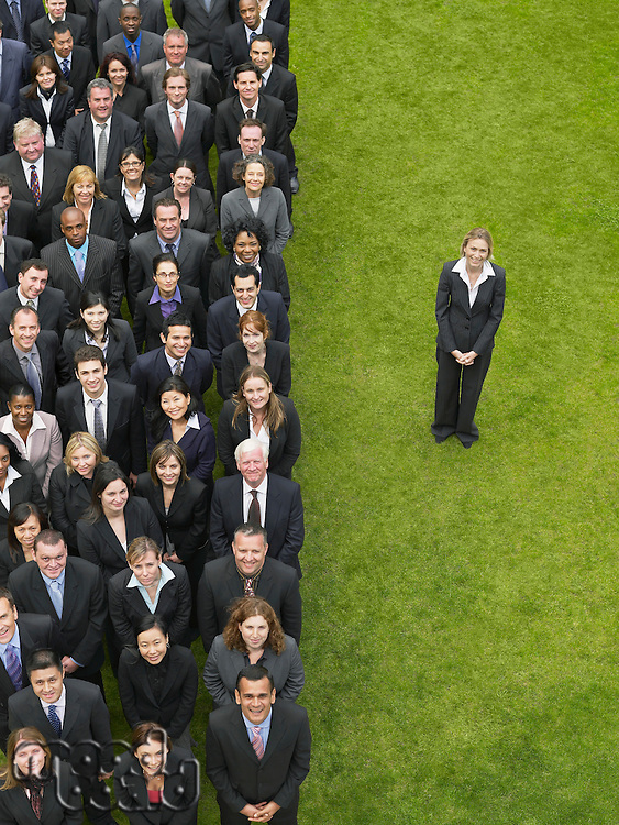 Business woman standing next to large group of business people in formation elevated view portrait