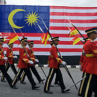 Malaysia's guard of honor walk past national flag during Independence Day celebration.